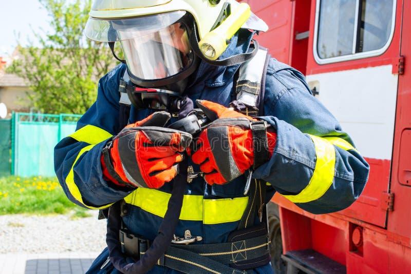 Πυροσβέστης που παίρνει έτοιμος για το firefight στοκ εικόνα