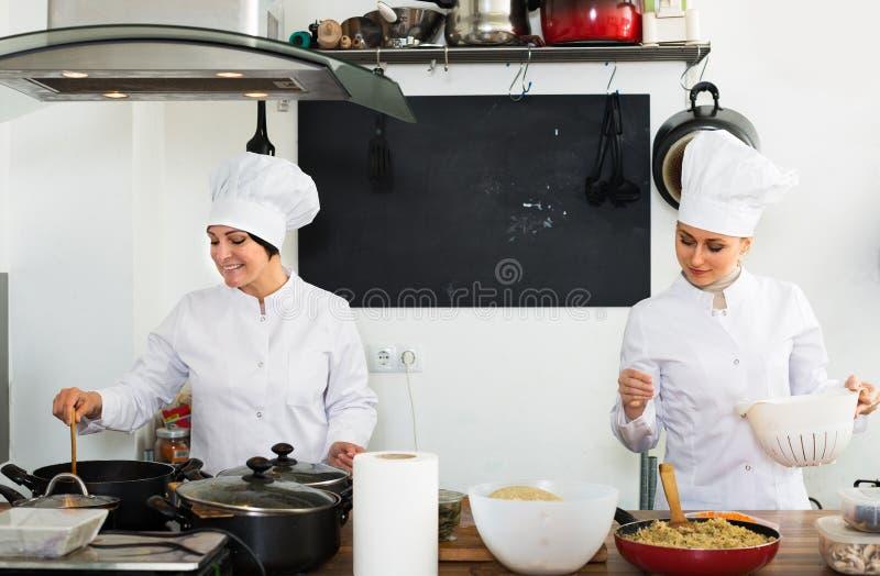 ¿ ï» зрелое и кашевар молодых женщин стоковые фото