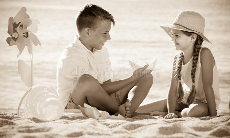 """ï""""演奏在海滩的¿男孩和女孩玩具 免版税库存照片"""