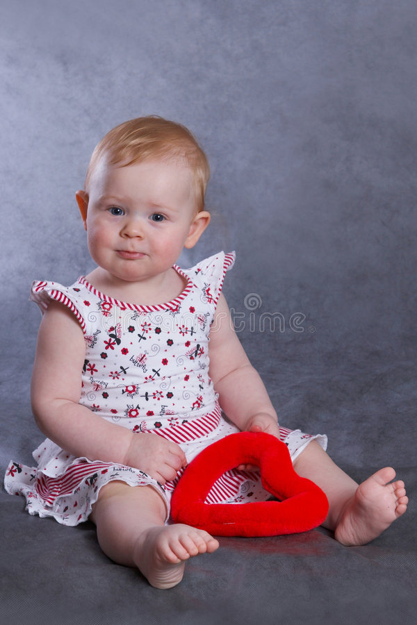 Нарру baby VALENTINE. Happy smiling baby 11 month old sitting stock photo
