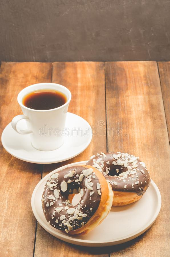 Ð¡offee break. White cup with black coffee and donat in chocolate glaze. Wooden background royalty free stock image