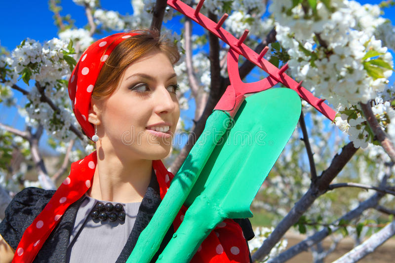 Ð¡ommunity work day. Portrait of young female with rakes on garden royalty free stock photography