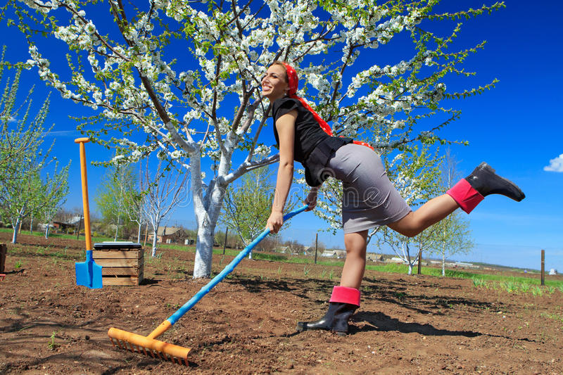 Ð¡ommunity work day. Portrait of young female with rakes on garden stock photos