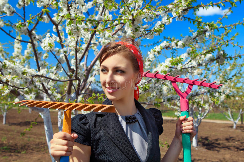 Ð¡ommunity work day. Portrait of young female with rakes on garden stock images