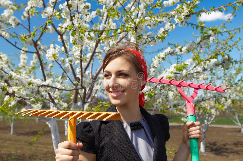 Ð¡ommunity work day. Portrait of young female with rakes on garden royalty free stock images
