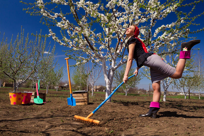 Ð¡ommunity work day. Portrait of young female with rakes on garden royalty free stock photos