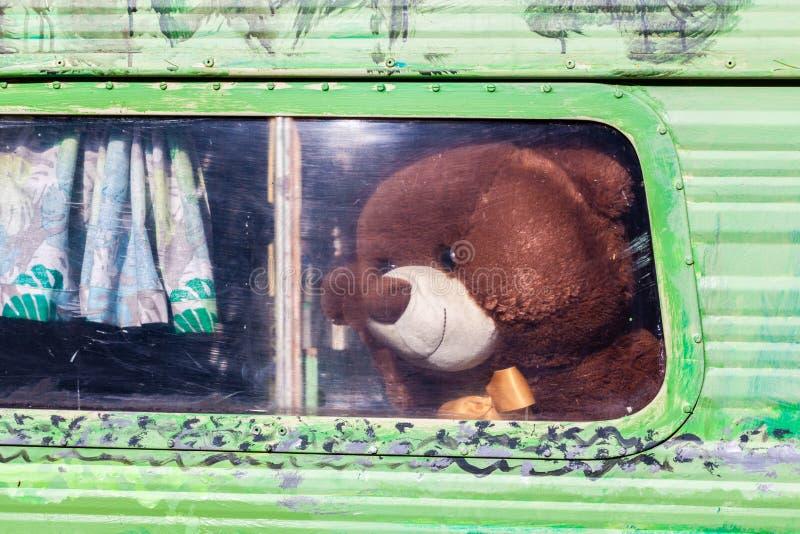 Тeddy björn som ser ut ur gammalt husvagnfönster arkivfoton