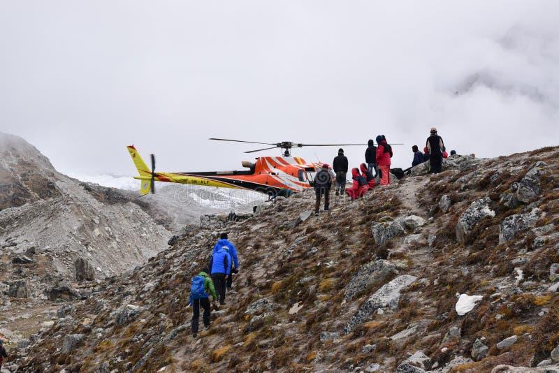 Аварийный вертолет тяпки опорожнения в весьма случаи погоды на снеге покрыл базовый лагерь EBC Эверест, Непал стоковое фото