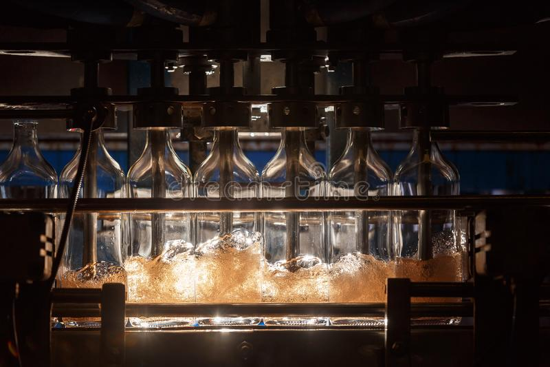 Автоматическая заполняя машина льет жидкость в стеклянные бутылки Продукция заваривать предпосылка промышленная стоковые фото
