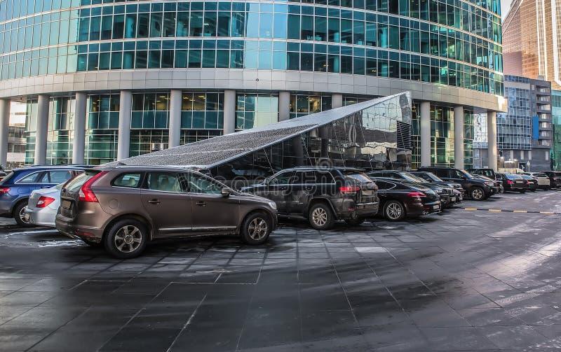 Автомобили в парковке около делового центра стоковая фотография