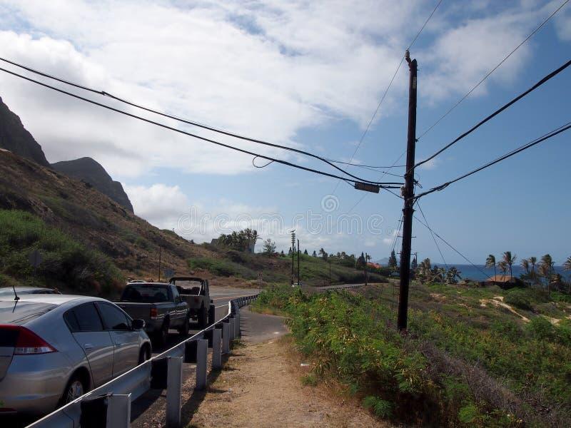 Автомобили припаркованные вдоль шоссе горы cliffside на Makapuu с протягивать голубой Тихий океан стоковые фото
