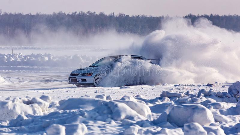 Автомобиль направил рельсами на покрытой снег дороге зимы Аварийное торможение Участвовать в гонке на льде озера стоковые изображения rf