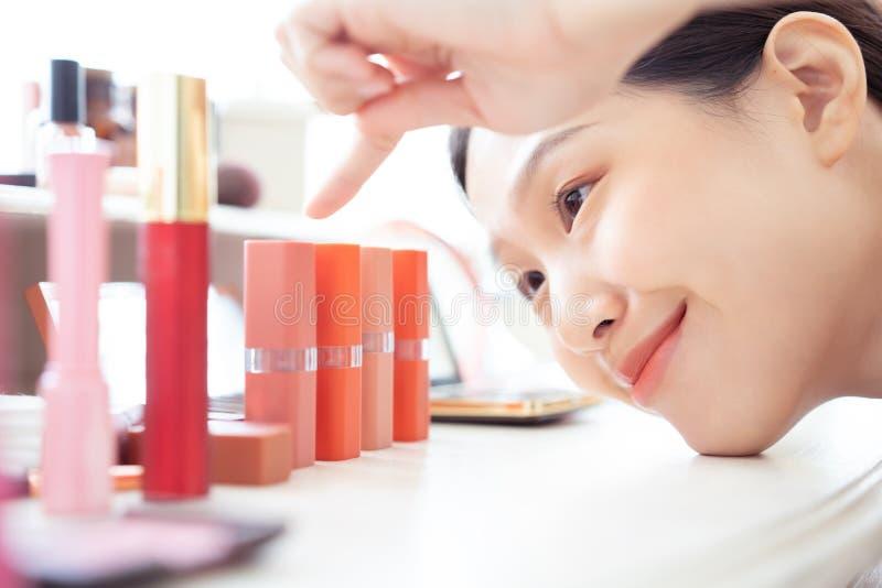 Азиатская женщина указывая выбирающ губную помаду стоковое изображение