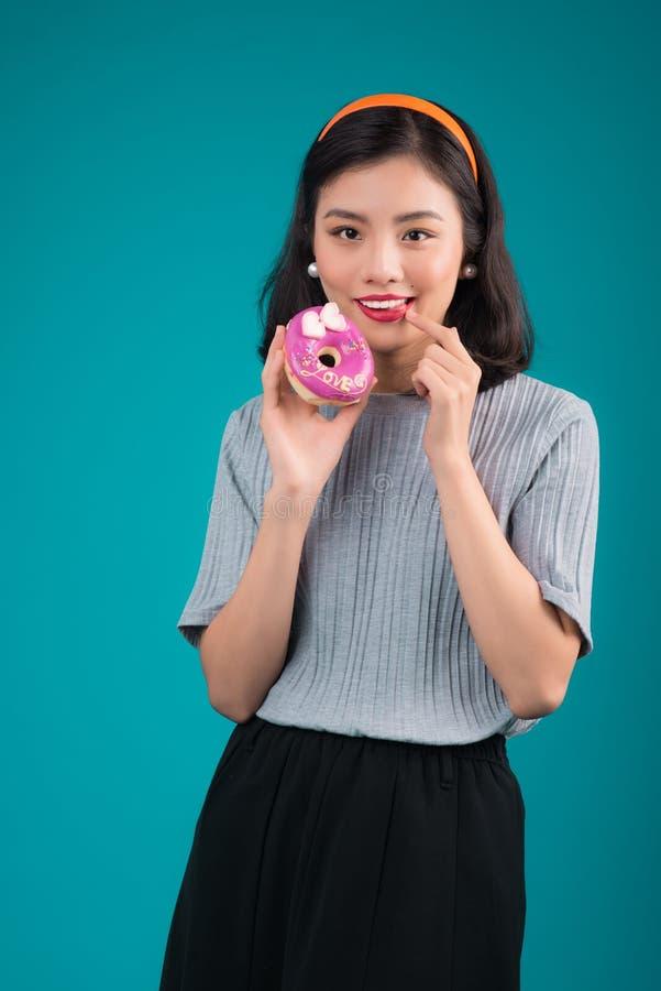 Азиатская девушка красоты держа розовый донут Ретро радостная женщина с помадками, десерт стоя над голубой предпосылкой стоковые изображения rf