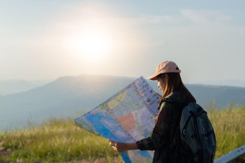 Азиатские люди молодых женщин с рюкзаками друзей идя совместно и смотря карту и принимая камеру фото дорогой и стоковые изображения