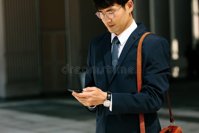 Азиатский бизнесмен идя outdoors используя умный телефон стоковое фото rf
