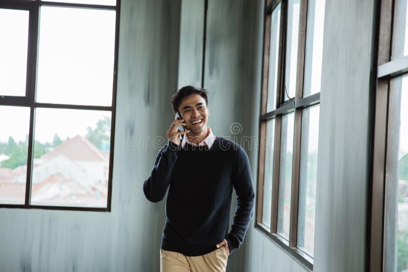 Азиатское счастье бизнесмена вызывая со смартфоном стоковая фотография rf
