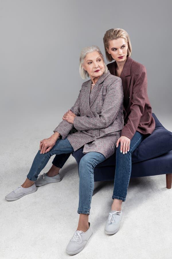 Активная старшая седая мать сидя между ногами ее красивой дочери стоковые изображения rf