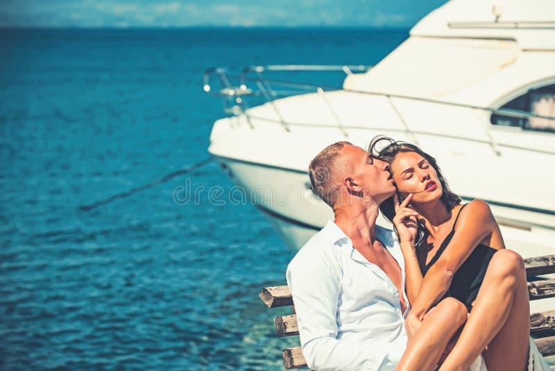 Активные пары на пляже ослабляют около роскошной яхты на стенде стоковое изображение rf