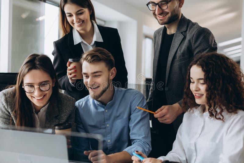 Анализировать свежие данные Группа в составе молодые уверенные бизнесмены обсуждая новый проект и усмехаясь пока тратящ время в стоковые фото