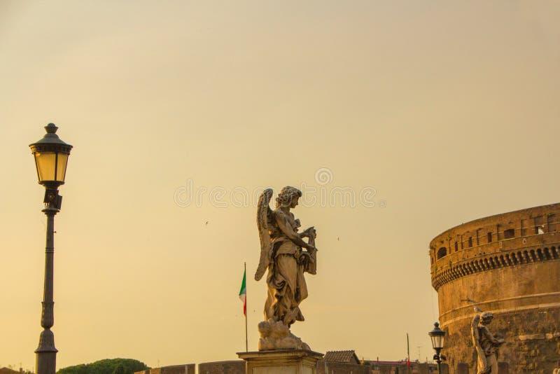 Ангел статуи на мосте над Тибром, около замка ангела Святого Заход солнца красивого вечера золотой на замке ангела Святого стоковое фото