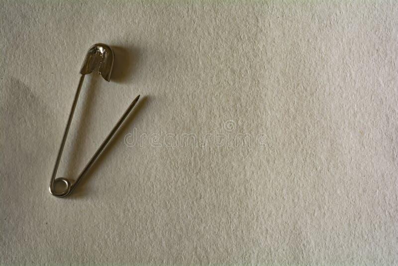 Английская булавка на предпосылке белой бумаги стоковое изображение