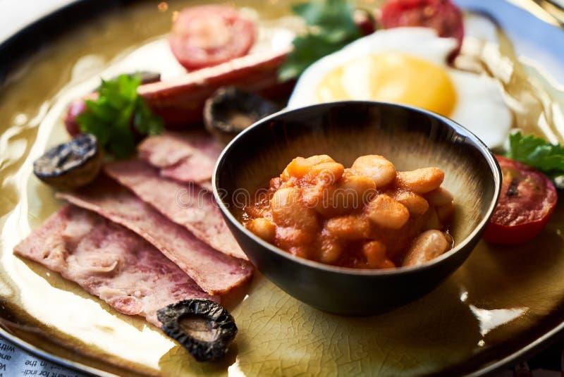 Английский завтрак с сосисками, взбитыми яйцами, беконом, грибами и фасолями стоковая фотография