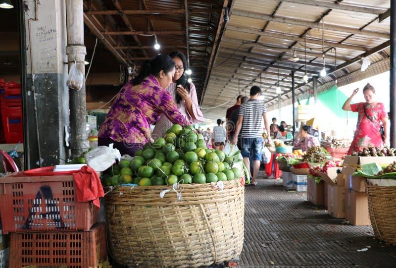Апельсин установил в бамбуковой корзине для надувательства и продавца плода на центральном рынке, крупном рынке сбыта с бесчислен стоковое изображение