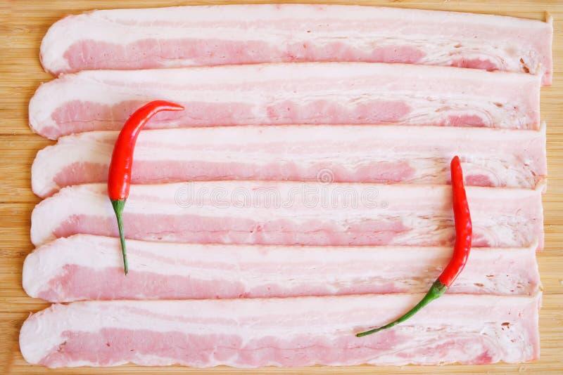 Аппетитные части перцев бекона свинины и красного chili лежат на естественной деревянной поверхности Дневной свет стоковое фото rf
