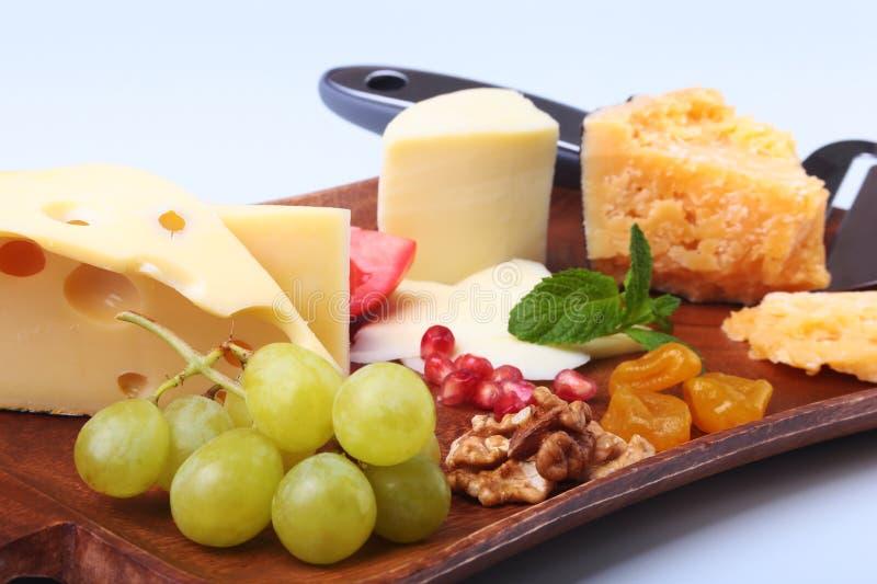Ассортимент сыра с плодоовощами, виноградинами, гайками и ножом сыра на деревянном подносе сервировки стоковое изображение
