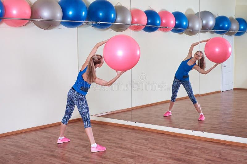 Атлетическая женщина делает тренировки на шарике фитнеса, внутри помещения спортзале стоковое изображение rf