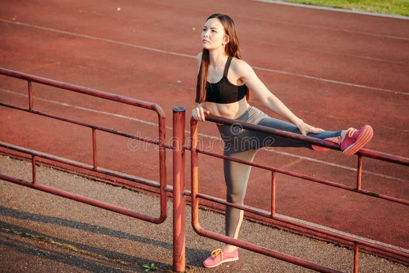 Атлетическая женщина делая подогрев на спортивной площадке стоковое фото rf