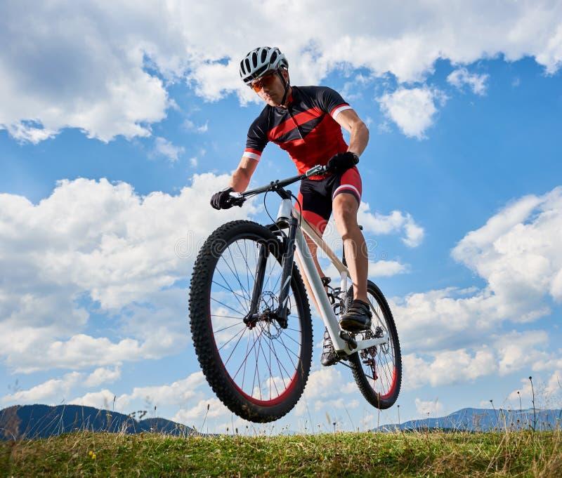 Атлетический велосипедист спортсмена в профессиональном летании sportswear в воздухе на его велосипеде на ярком голубом небе стоковая фотография rf