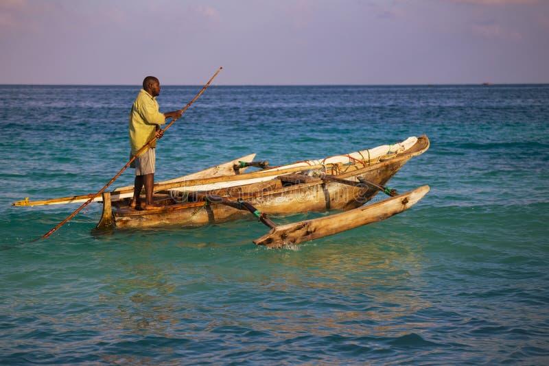 Африканский человек - рыболов на старой традиционной деревянной шлюпке на поверхности океана стоковое изображение