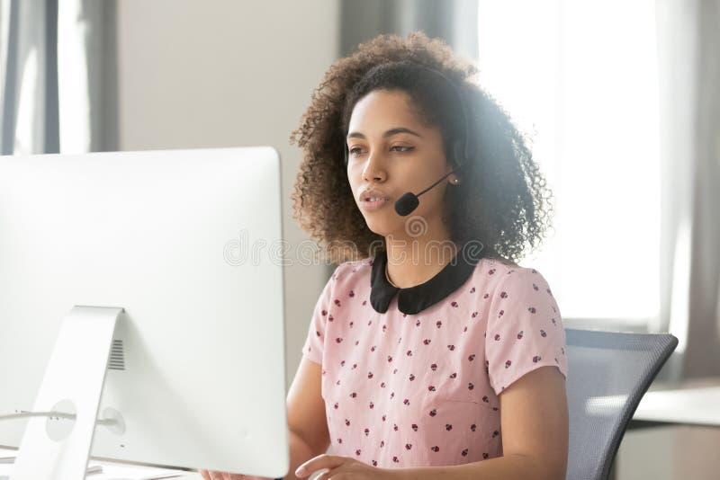 Африканский оператор центра телефонного обслуживания в беспроводном шлемофоне говоря используя компьютер стоковая фотография