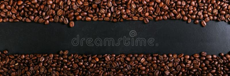 Ароматность зажарила в духовке кофейные зерна на деревенской столешнице, коричневой предпосылке знамени стоковые фото