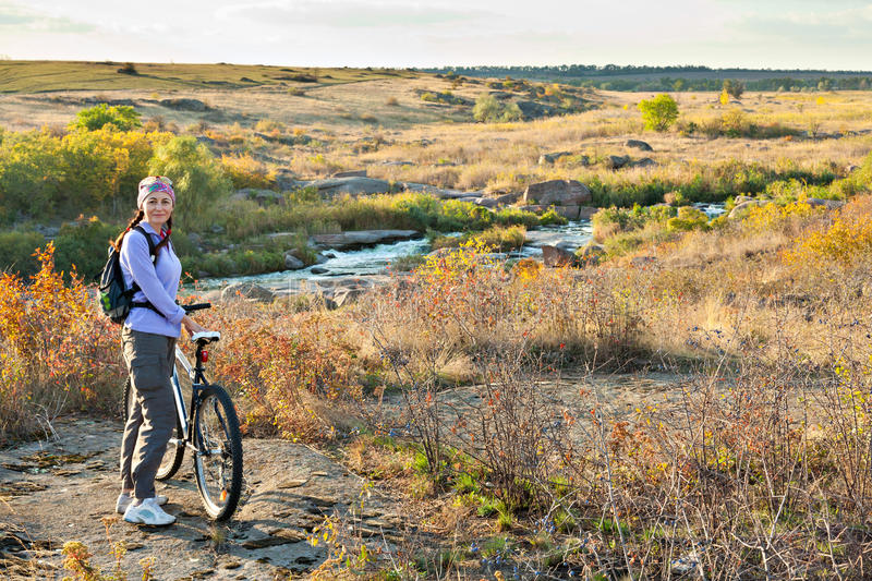 Аdult woman standing next to a mountain bike. And looking at the camera on a river and hills background stock photos
