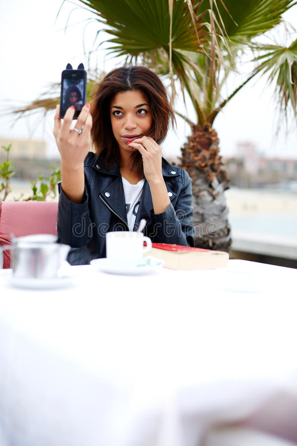 Аttractive hipster young woman taking a picture of herself on her cell phone. Afro american female taking fun self portrait with smartphone camera while stock photography