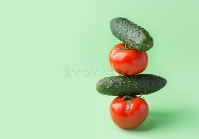Балансируя стог свежих сырцовых органических огурцов томатов в пирамиде на предпосылке салата зеленой Сбалансированный vegan диет стоковое фото rf