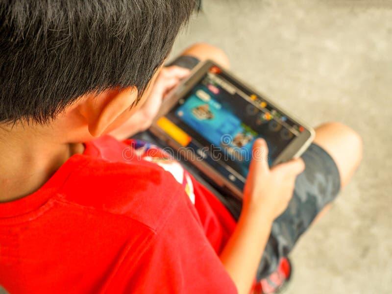 БАНГКОК ТАИЛАНД, 15-ое апреля 2017: Ребенк играя игры на мобильном телефоне стоковые изображения rf