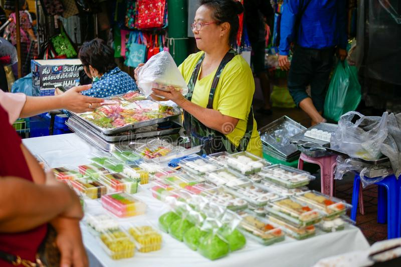БАНГКОК, ТАИЛАНД - 29-ОЕ ДЕКАБРЯ 2017: Торговцы продают тайские помадки к клиентам на рынке Yaowarat в Бангкоке стоковые изображения