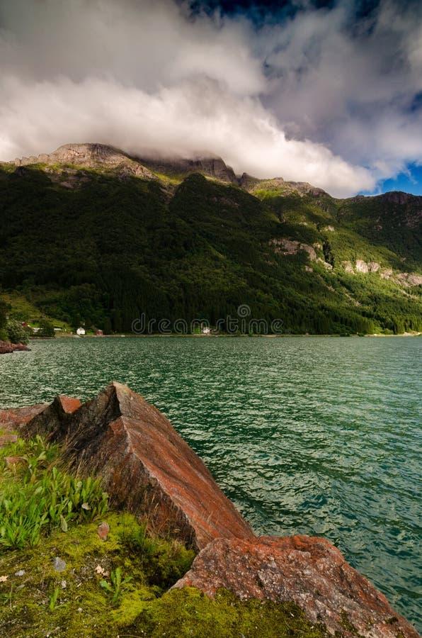 Банк озера Sandvinvatnet Самая высокая гора региона, Rossnos, на заднем плане стоковая фотография