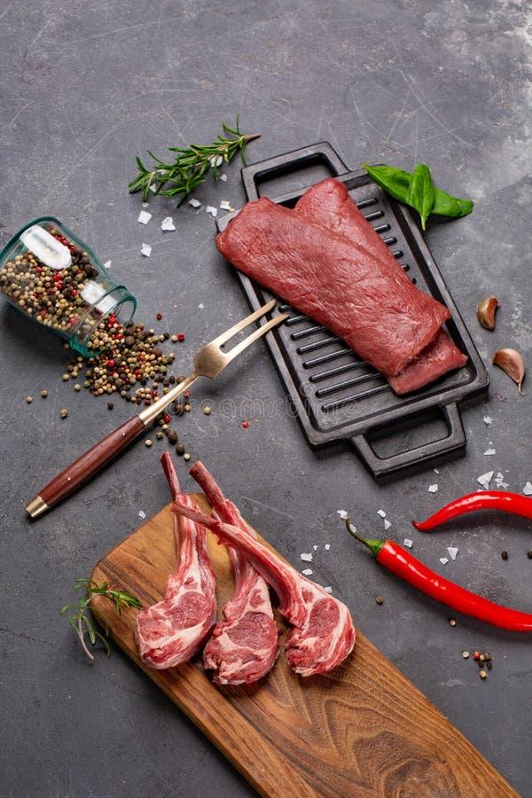 Баранина мяса сырцовая свежая на специях Chesno и Розмари косточки на черной предпосылке стоковое изображение rf