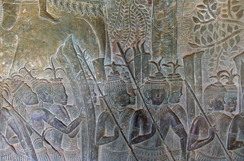 Барельеф в древнем храме Angkor Wat, Siem Reap, Камбодже Военная сцена на каменной стене Стародедовский барельеф стоковое изображение