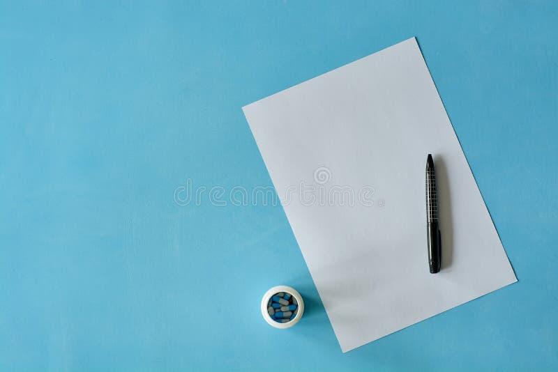 Белая бумага листа с черной ручкой и покрашенными различными таблетками стоковые фото