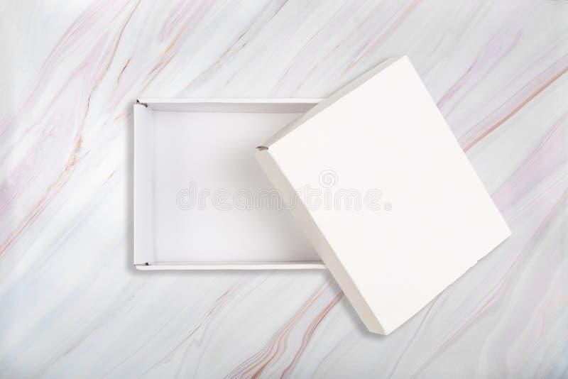 Белая картонная коробка с открытой крышкой на естественной мраморной предпосылке картины Открытая белая коробка на мраморной текс стоковые фотографии rf