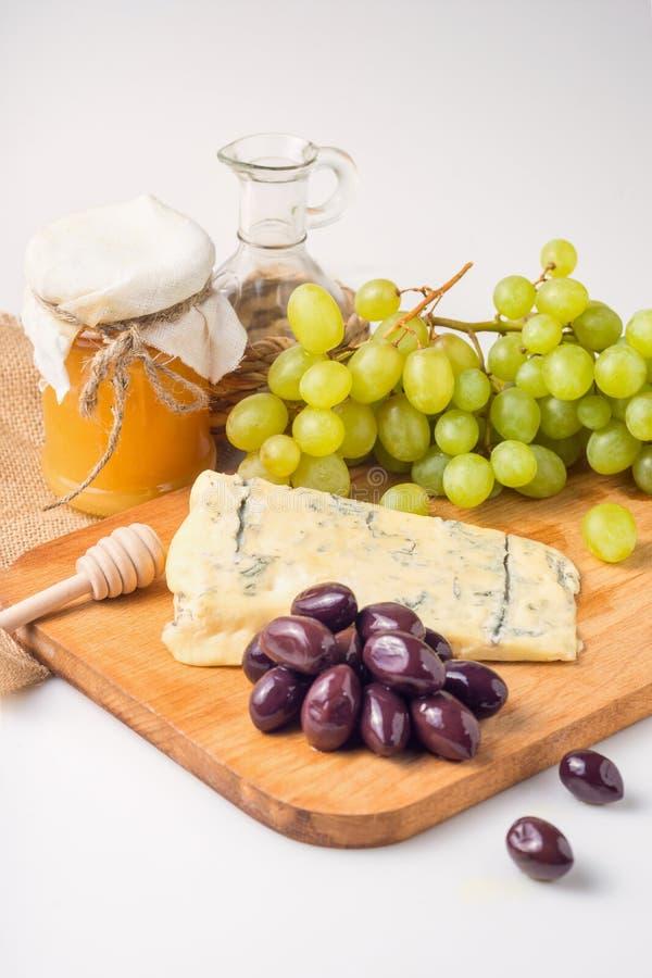 Белая плита сыра с оливками, мед, виноградины Ассортимент закуски вина, закуски или изысканного обедающего Взгляд сверху стоковое изображение rf