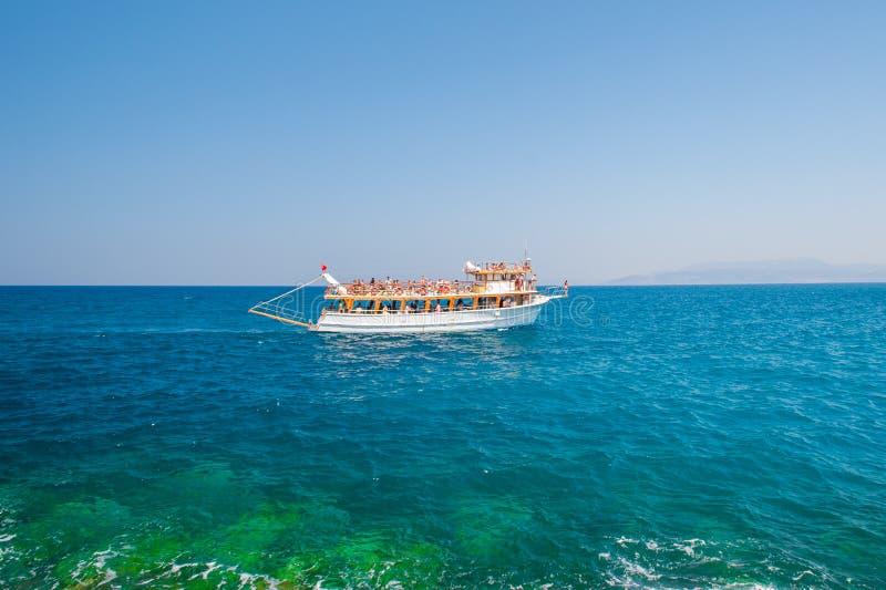 Белая шлюпка, корабль, яхта, плавая с туристами по побережью стоковое фото