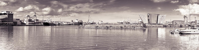 БЕЛФАСТ, ВЕЛИКОБРИТАНИЯ - 24-ОЕ АВГУСТА 2016: Панорамный вид гавани Белфаста с титаническим дворцом музея - тонизированное изобра стоковая фотография rf