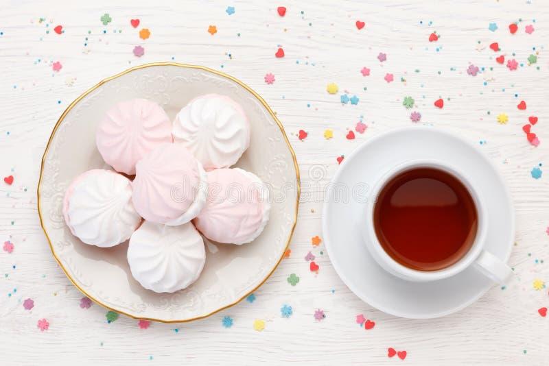 Белые и розовые zephyr и чашка чаю зефира на деревянном столе стоковая фотография